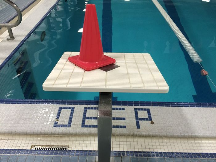 Traffic cone on diving platform by swimming pool