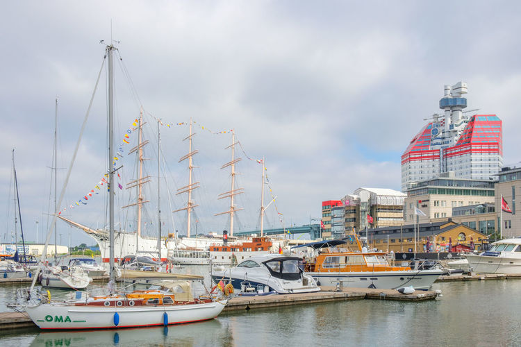 Sailboats moored at harbor in city against sky