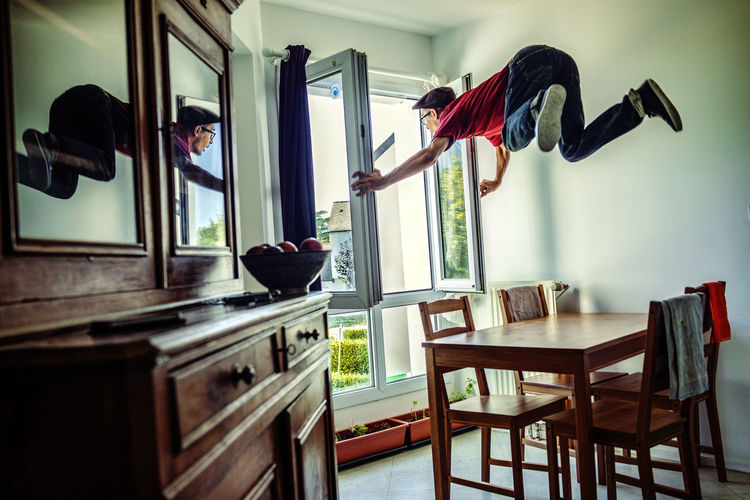 Man holding window frame while levitating at home