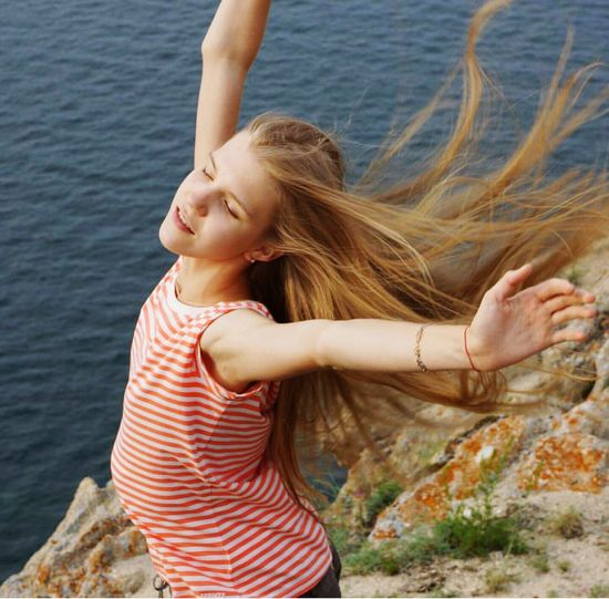 High angle view of young woman with arms outstretched standing on cliff