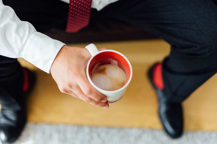 Male hand holding a cup of coffee from high angle view Lifestyle Red Cafe Cappuccino Close-up Coffee - Drink Coffee Cup Drink Food And Drink Freshness Frothy Drink High Angel View High Angle View Holding Human Hand Human Leg Indoors  Latte Leisure Activity Lifestyles Men One Person Real People Refreshment Sitting