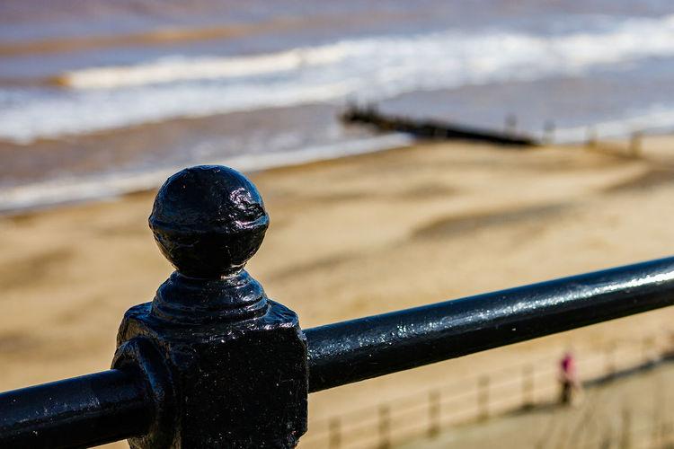 Close-up of metal railing on beach