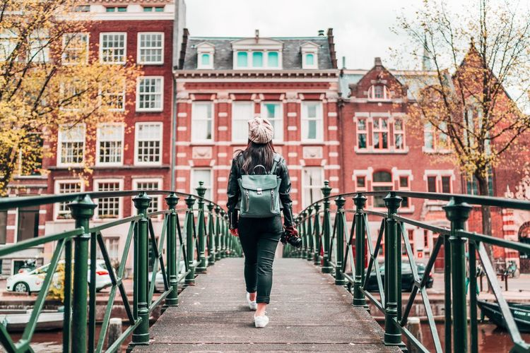 Woman walking on footbridge in city