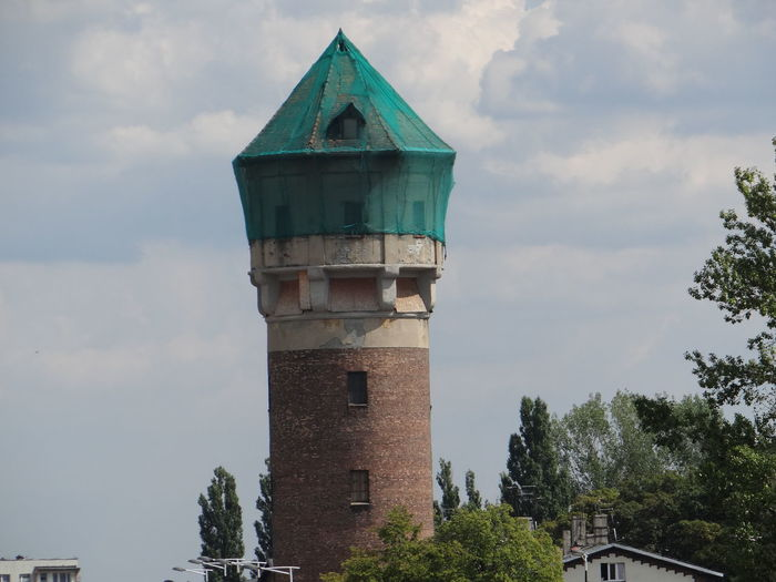 Low angle view of old tower amidst buildings against sky