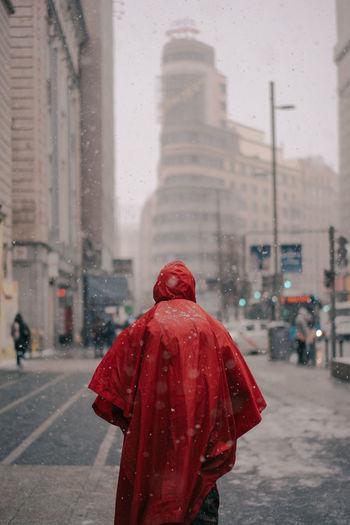 Rear view of person walking on wet street in rainy season