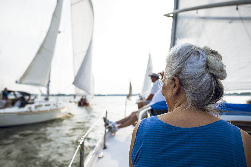 Rear view of woman on sailboat sailing in sea