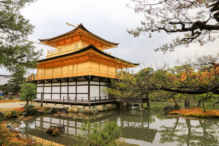 Temple by lake and building against sky