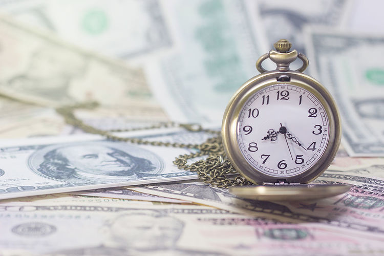 Close-up of clock on us paper currency