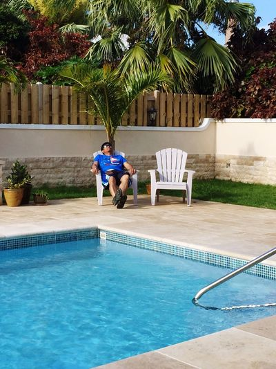 Man relaxing on chair at poolside