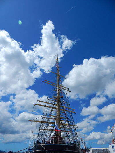 Low angle view of ship moored at harbor against blue sky