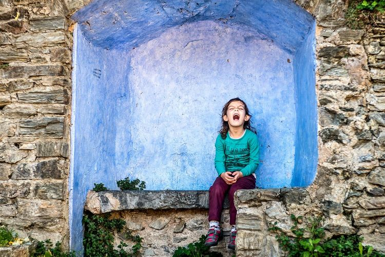 Portrait of laughing girl sitting outdoors