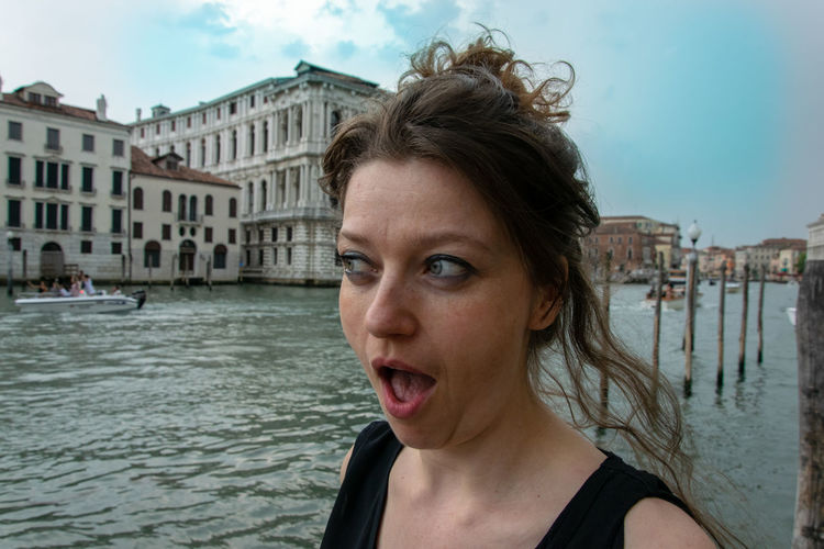 Mid adult woman with mouth open standing by canal against sky in city