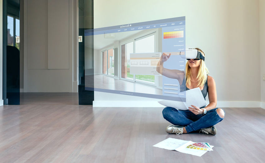 Young woman using decoration application with virtual reality glasses Blonde Copy Space Decorating Glasses Happiness Happy Horizontal Virtual Reality Woman Caucasian Color Decoration Female Girl Home Interior Lifestyles New Home One Person Palette Plans Virtual Glasses Vr Watching Young Adult Young Women
