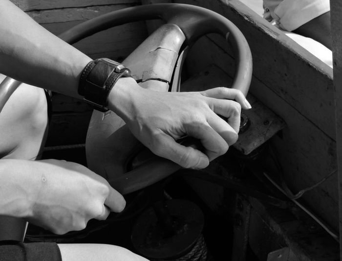 Midsection of man holding steering wheel
