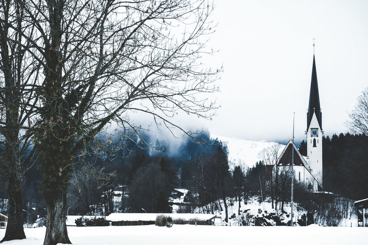 Wintery town Snow Cold Temperature Winter Tree Plant Nature Building Exterior Sky Built Structure Architecture Day Beauty In Nature Covering Bare Tree Building No People Scenics - Nature Tranquility Tranquil Scene Outdoors Snowcapped Mountain Church Wintertime Winter Town Small Town