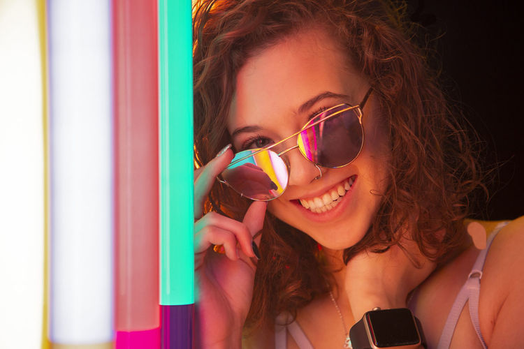 Portrait of a smiling young woman against neon lights