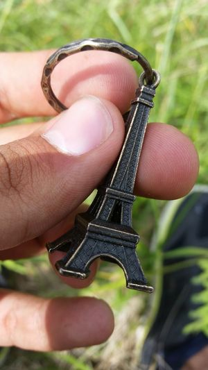 Cropped hand holding eiffel tower key ring on sunny day