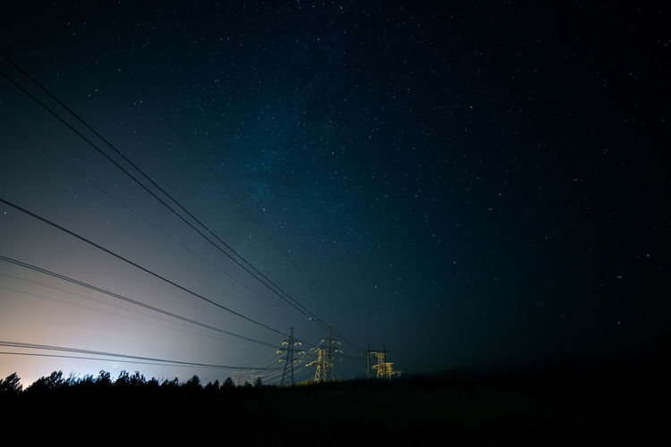 Incredible night sky with stars, Milky Way passing over power line in long exposure timelapse. Beautiful panorama view. Nature in the countryside. Astro photography. Sky Cable Electricity  Star - Space Night Power Line  Scenics - Nature Electricity Pylon Astronomy Beauty In Nature Connection Technology Power Supply Space Tranquil Scene Fuel And Power Generation No People Nature Low Angle View Tranquility Outdoors Telephone Line Milky Way Astrophotography Power Line