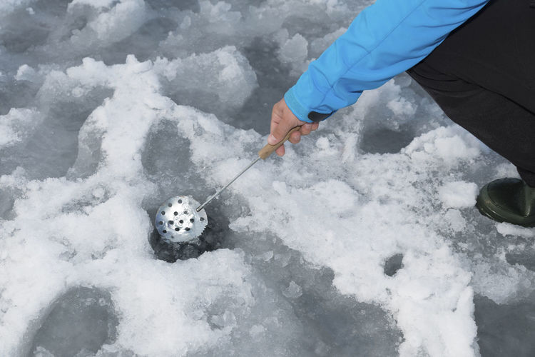 Low section of man ice fishing