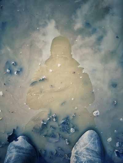 Low section of person in sea against sky during winter