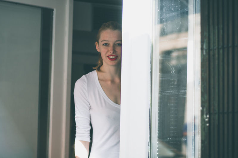 Portrait of happy young woman standing at house entrance