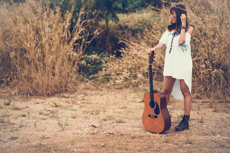 Musical Instrument Music One Person String Instrument Full Length Young Adult Musical Equipment Casual Clothing Plant Young Women Guitar Leisure Activity Standing Nature Musician Land Real People Day Acoustic Guitar Fashion Outdoors Hairstyle Beautiful Woman