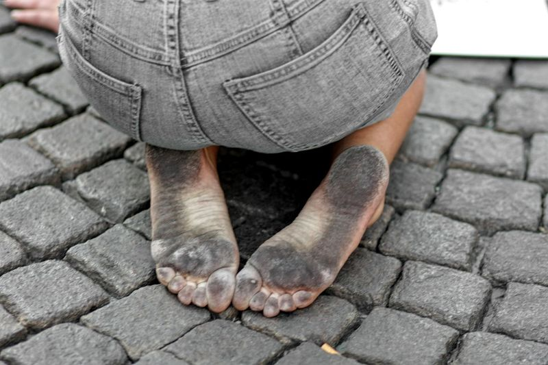 High angle view of person with dirty soles kneeling on cobbled footpath