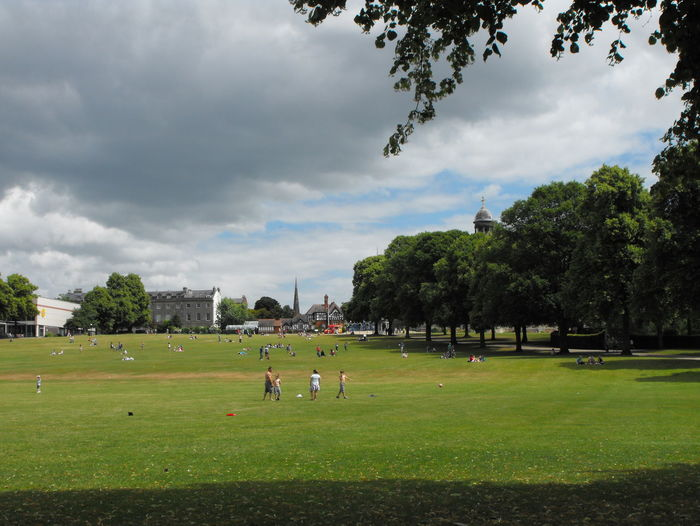 People playing in park against sky