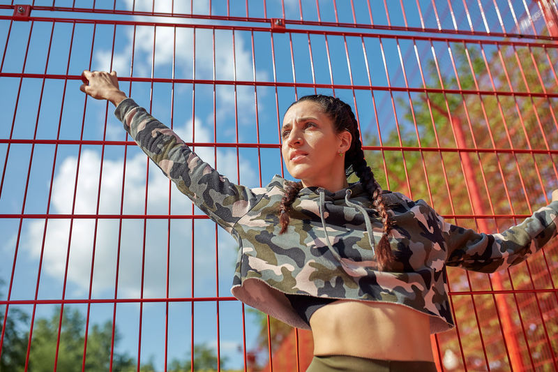 Low angle view of young woman standing against fence
