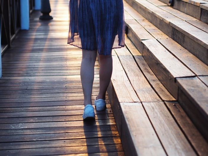 Low section of woman walking on hardwood floor