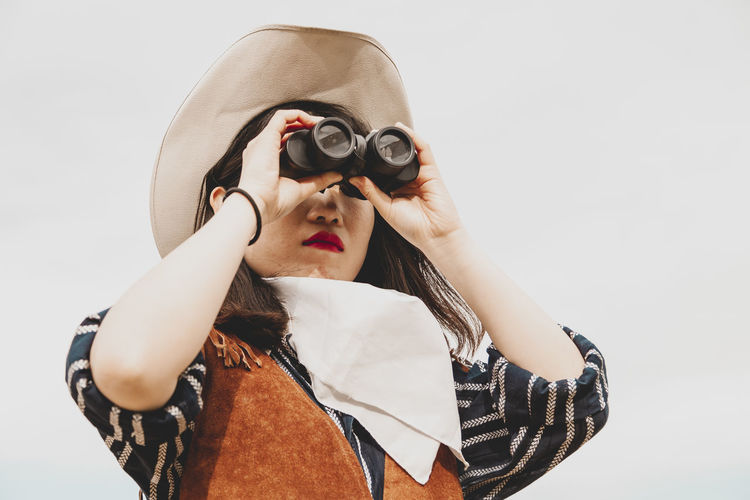 Young woman looking through binoculars against white background