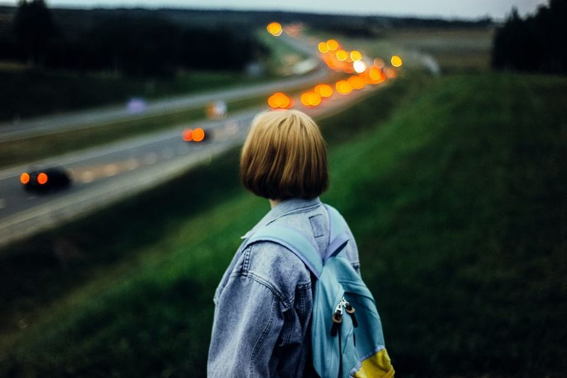 Woman Standing With Backpack Against Road At Dusk
