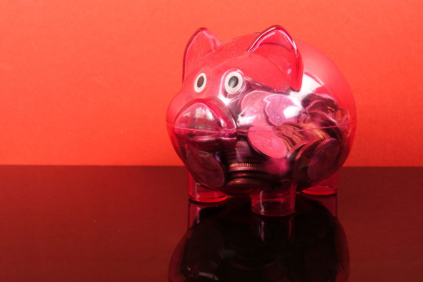 Saving concept with red piggy bank on red background. Piggy Bank Animal Representation Art And Craft Celebration Close-up Coin Colored Background Conceptual Photography  Disguise Glass - Material Indoors  Investment Mask Mask - Disguise No People Piggy Bank Red Red Background Representation Saving Concept Single Object Still Life Studio Shot Table Transparent