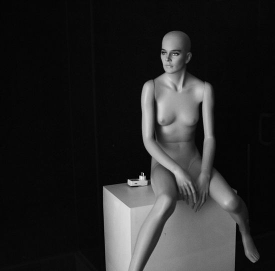 Mannequin with box against black background