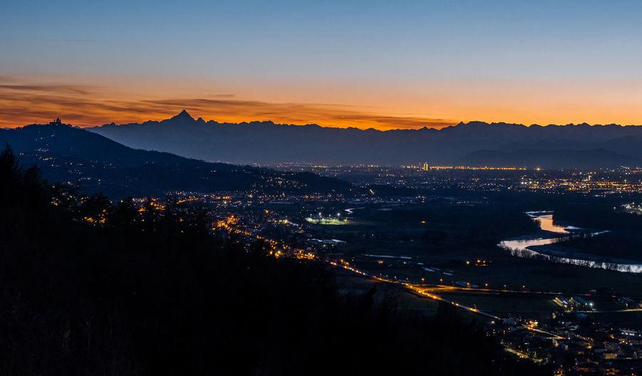 High angle shot of illuminated cityscape against sky during sunset