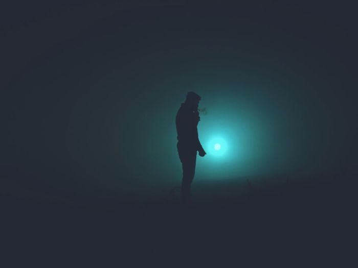 Silhouette people standing on illuminated light at night