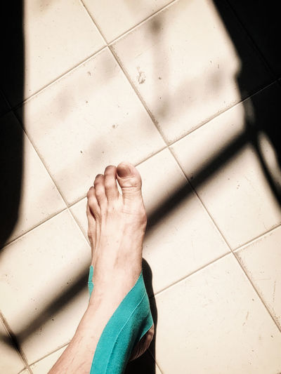 Low section of person on tiled floor