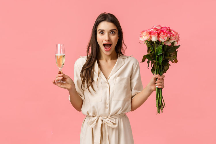 Portrait of woman with pink rose against gray background