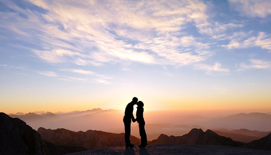 Silhouette man kissing woman while standing against cloudy sky during sunset