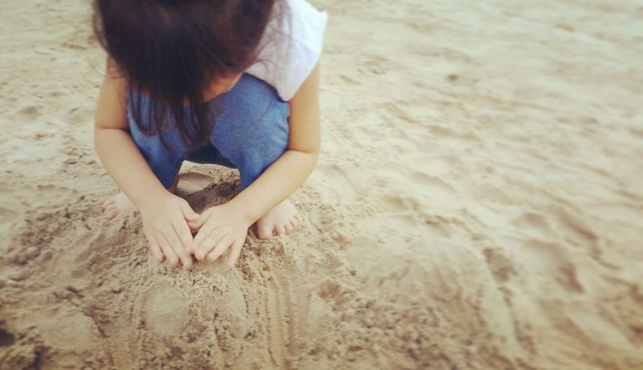 High angle view of girl playing while crouching on sand