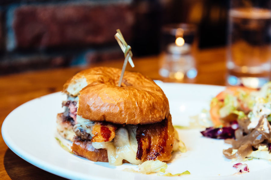 Close up of Bacon Burger Bacon Cheese Burger Burger Manhattan Bacon Baked Burger Cheese Close-up Focus On Foreground Food Food And Drink Freshness Glass Indoors  Indulgence Meat No People Plate Ready-to-eat Sandwich Serving Size Snack Still Life Table Temptation Unhealthy Eating