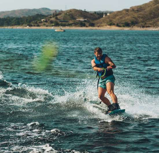 Full length of man wakeboarding in sea