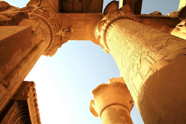Hieroglyphics on columns against clear sky
