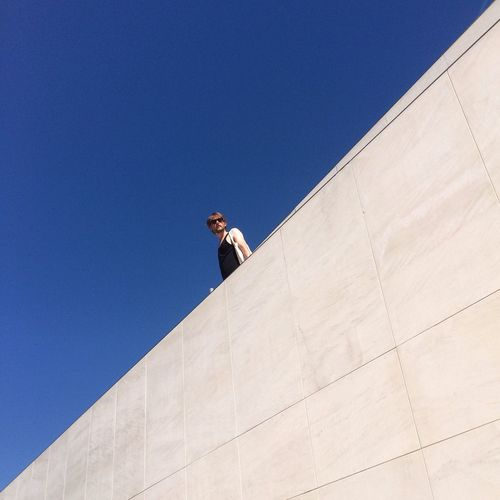Low angle view of man standing on building terrace against clear blue sky