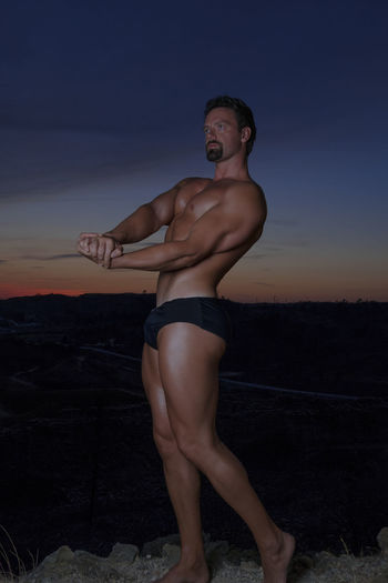 Shirtless bodybuilder exercising on rock against sky during sunset