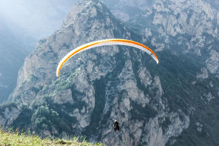 Man paragliding on mountain peak