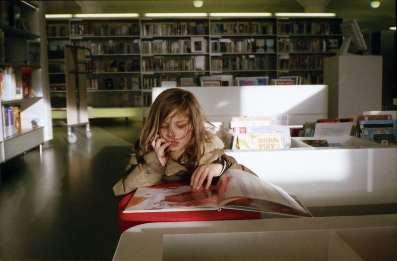 Girl reading book while sitting at table in library