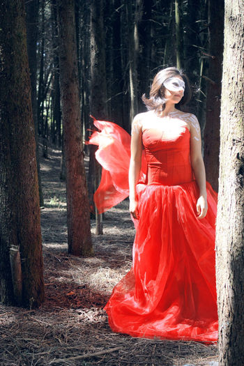 Woman in red dress standing by trees in forest
