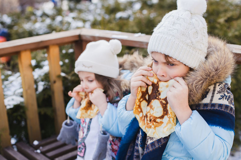 Girls eating tortilla while standing outdoors