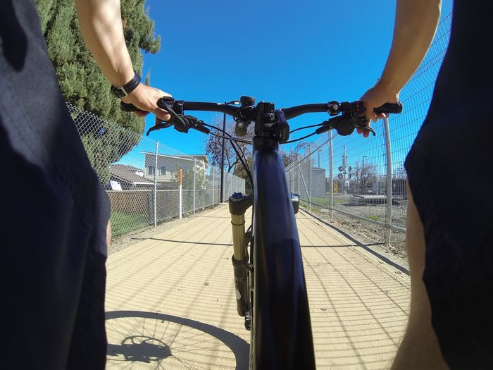Man riding bicycle on footpath against clear blue sky